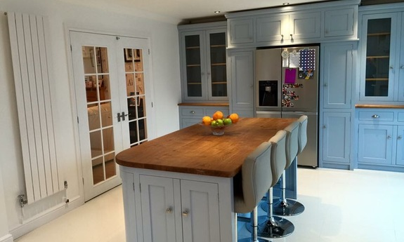 Tailor made solid wood shaker style kitchen finished in Farrow & Ball Parma Grey.Fully bespoke island site with wide plank solid oak surface top.