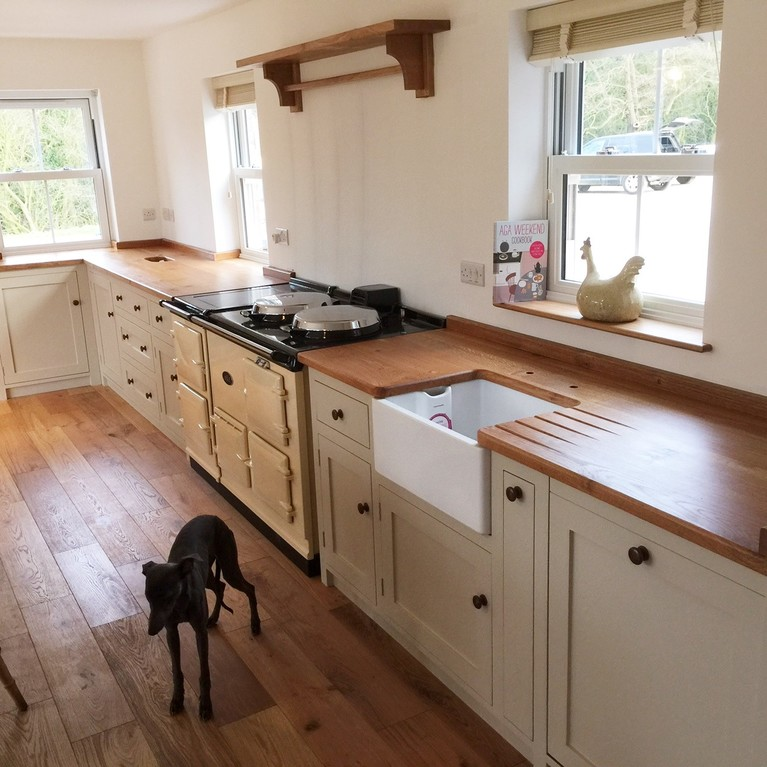 Bespoke hand built kitchen in solid wood shaker style with wide plank oak surface tops .Belfast sink.