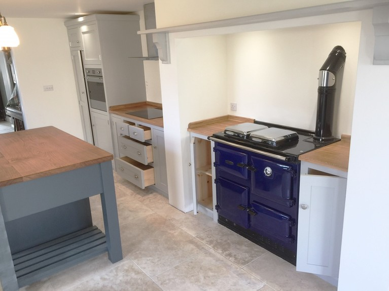 Individually tailored shaker style fitted kitchen hand made from solid wood painted in Farrow & Ball pavillion grey. Fully bespoke island site with wide plank solid oak surface top.
